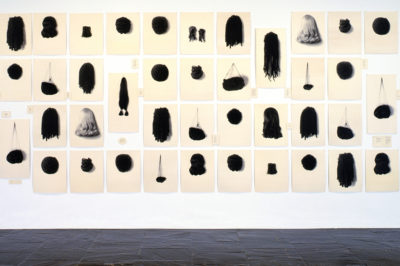 Lorna Simpson Wigs II, 1994-2006 Serigraph on 71 felt panels (images and text) 98 x 265 in overall. Courtesy the artist, Salon 94, New York; and Galerie Nathalie Obadia, Paris / Brussels © Lorna Simpson